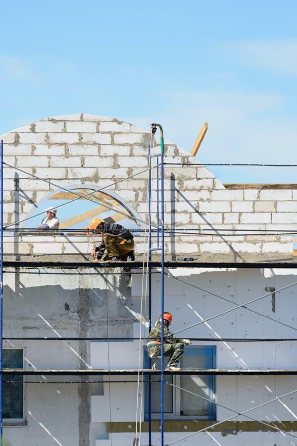 Materiais de construção do elevador dos construtores dos trabalhadores no andaime fotos de stock