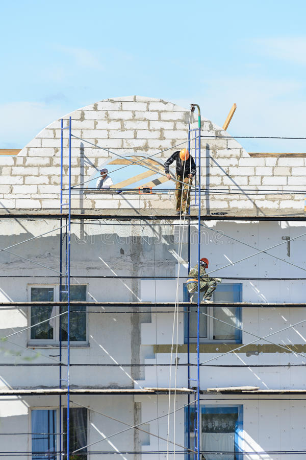 Materiais de construção do elevador dos construtores dos trabalhadores no andaime fotos de stock royalty free