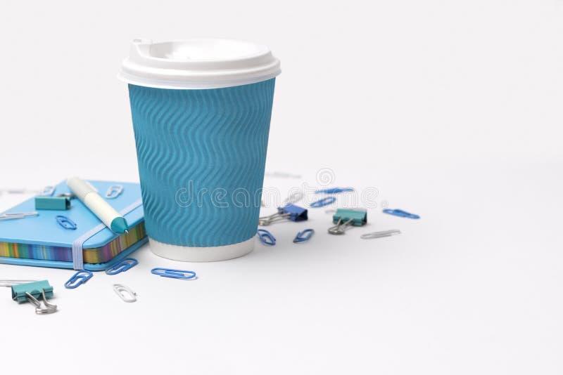 Materiais de escrit?rio azuis Copo, pena de papel e blocos de notas de café isolados no fundo branco fotos de stock royalty free
