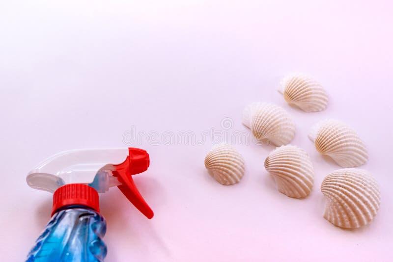 Materiais de limpeza com perfume marinho Pulverizador para o líquido, escudos no fundo cor-de-rosa pastel imagens de stock royalty free