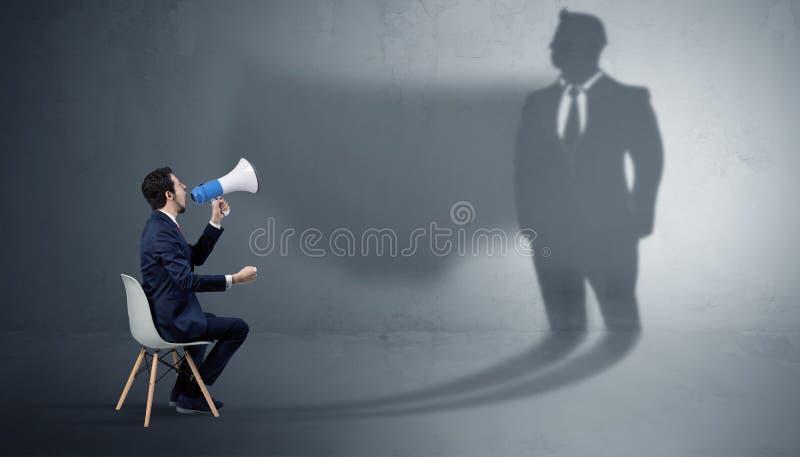Materiais ficando e de oferecimento do homem de neg?cios a uma sombra enorme do homem de neg?cios imagens de stock royalty free