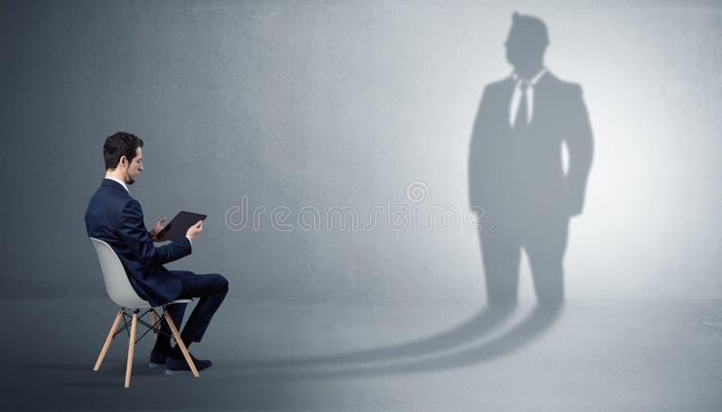 Materiais ficando e de oferecimento do homem de neg?cios a uma sombra enorme do homem de neg?cios fotos de stock