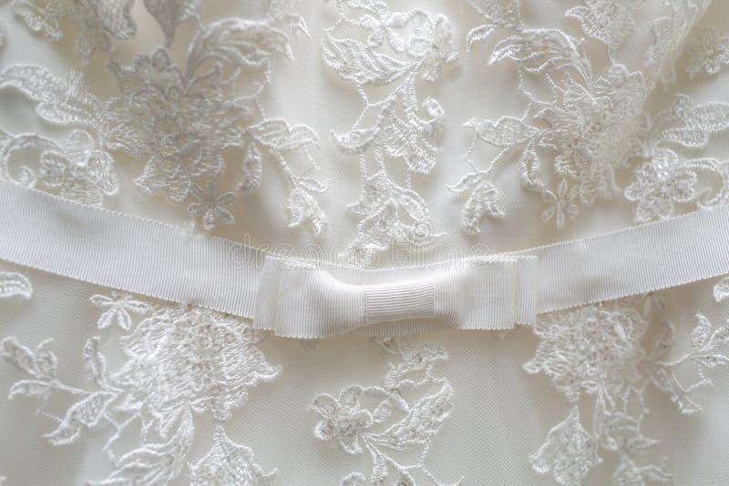 Material blanco de Tulle con los modelos en la forma de las flores y un arco en el centro foto de archivo libre de regalías