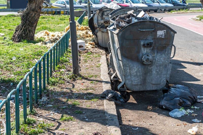 Material de desperd?cio perigoso despejado na rua urbana da cidade perto das latas de lixo que poluem e que desarrumam o ambiente fotografia de stock