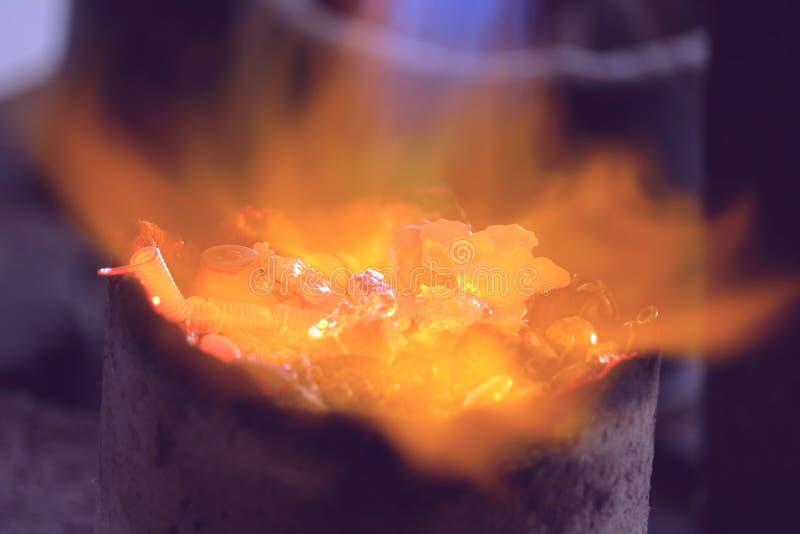 Material de prata com a chama no cadinho pequeno fotografia de stock