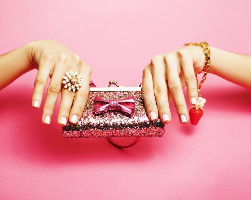 Material des kleinen Mädchens für Prinzessin, Frauenhände, die kleinen netten Geldbeutel auf rosa Hintergrund halten lizenzfreies stockfoto