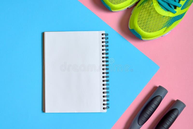 Material desportivo com sapatas, corda de salto e o caderno vazio no rosa e no fundo pastel azul, espaço da cópia Vista superior, imagens de stock