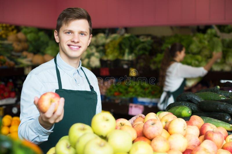 Material i förklädet som säljer äpplen arkivfoton