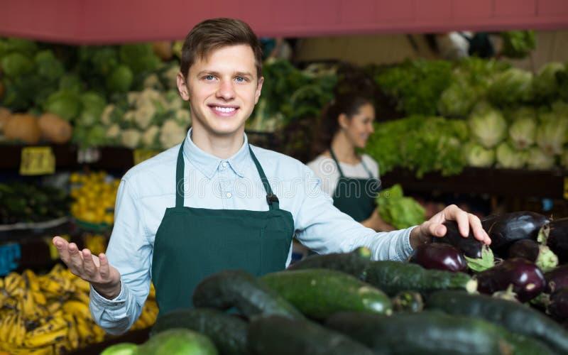 Material i förklädet som säljer den gröna gurkan på marknadsplatsen arkivfoto