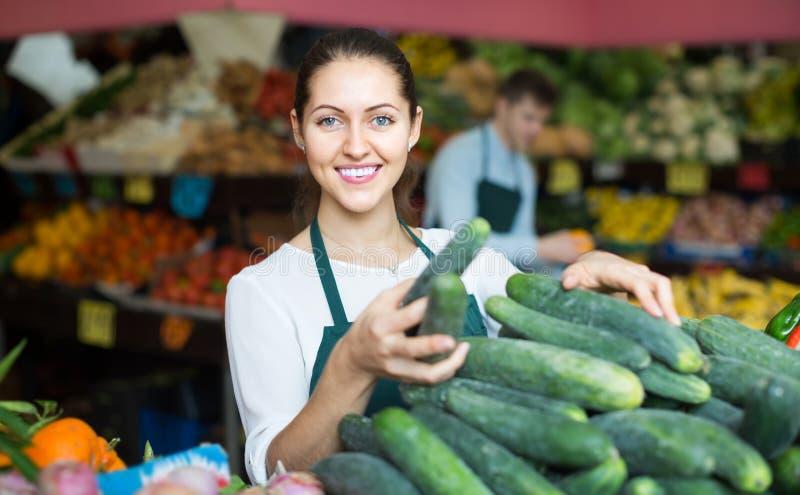 Material i förklädet som säljer den gröna gurkan på marknadsplatsen arkivbild