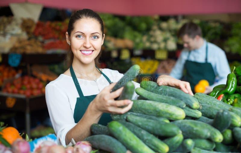Material i förklädet som säljer den gröna gurkan på marknadsplatsen arkivbilder