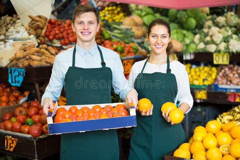 Material no avental que vende laranjas doces, limões e tangerinas fotos de stock royalty free