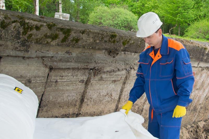 Material para proteger la superficie del suelo, desenrollando un trabajador en un uniforme azul y un casco blanco en un emplazami imagen de archivo