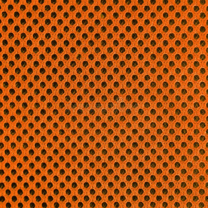 Material poriferous poroso respirável alaranjado para a ventilação do ar com furos Textura de nylon material do Sportswear quadra imagens de stock royalty free