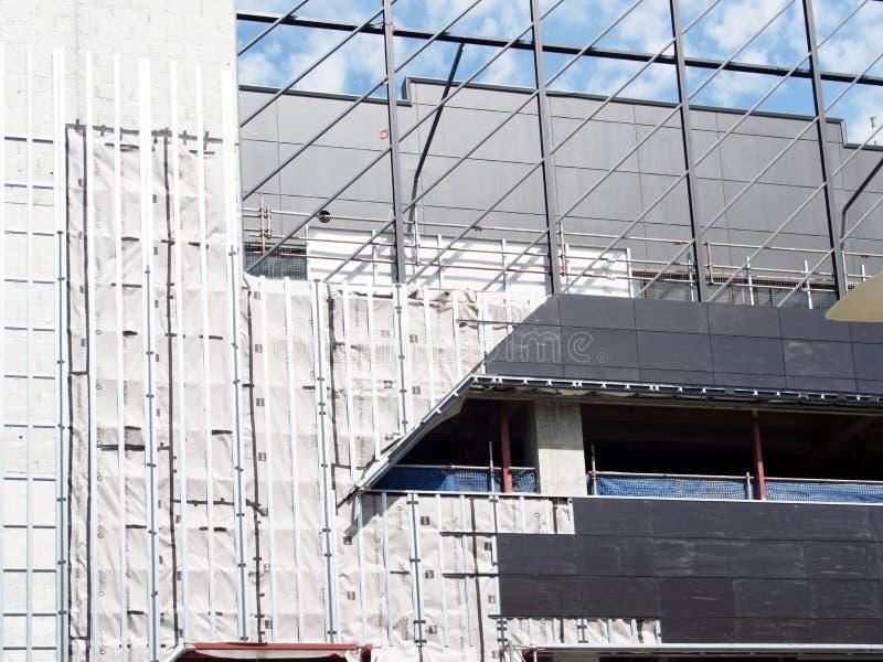 Material till byggnadsställning och Cladding på Mitt--löneförhöjning konstruktionsplats arkivfoto