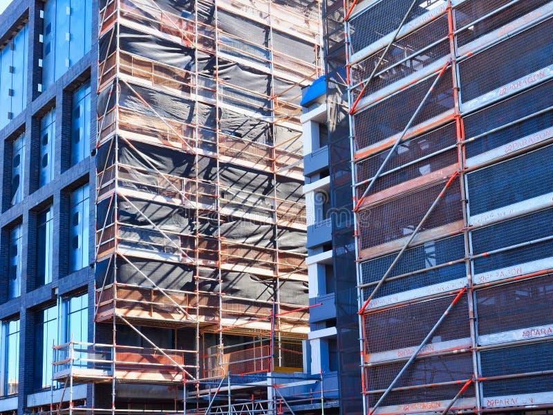 Material till byggnadsställning och säkerhetsingrepp på modern byggandeplats royaltyfri fotografi