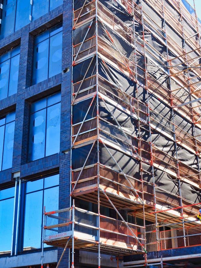 Material till byggnadsställning och säkerhetsingrepp på modern byggandeplats arkivbild