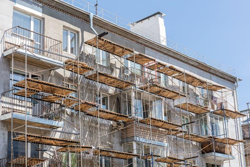 Material till byggnadsställning på stads- hyreshus fasadrenovering av ol royaltyfri fotografi