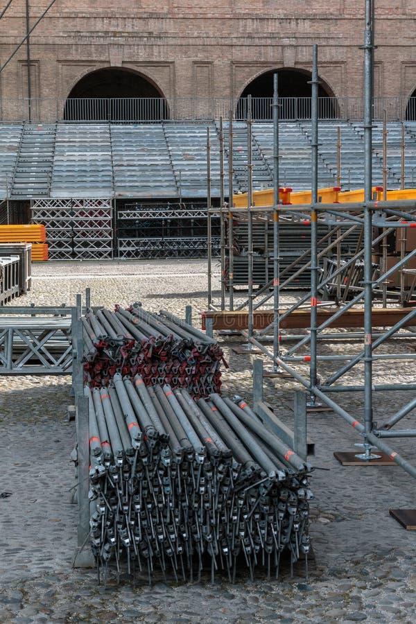 Material till byggnadsställningbeståndsdelkonstruktion och staplade Poles för etappSt arkivbild