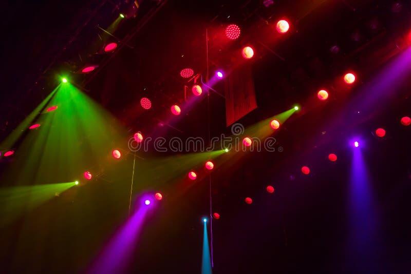 Materiale di illuminazione sulla fase di un teatro o di una sala da concerto I raggi di luce dai riflettori Alogeno e lampadine p fotografia stock