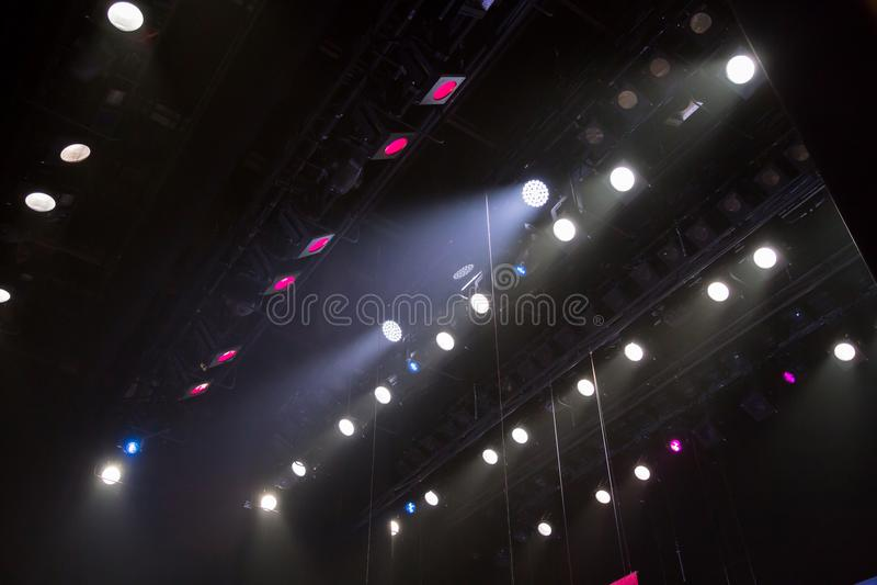 Materiale di illuminazione sulla fase di un teatro o di una sala da concerto I raggi di luce dai riflettori Alogeno e lampadine p immagini stock libere da diritti