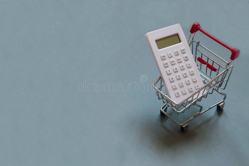 Materiale di riempimento del carrello o del carrello con il calcolatore bianco su fondo grigio Spazio della copia per testo e/o i fotografia stock libera da diritti