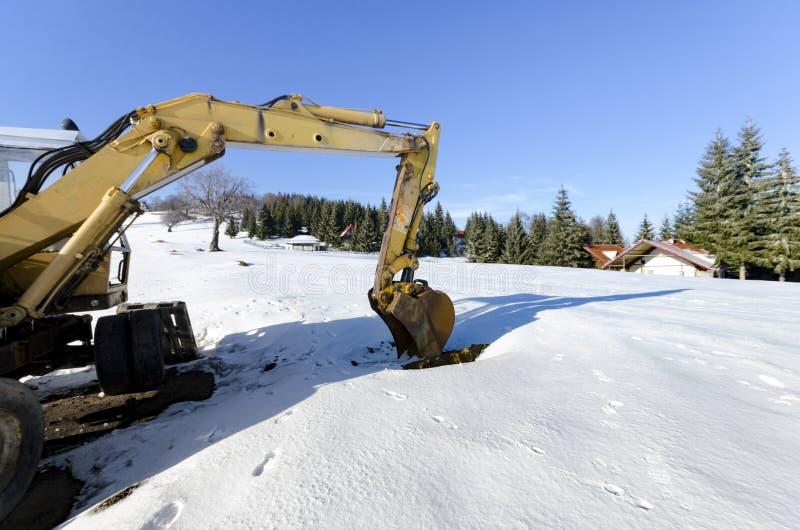 Materiale industriale del suolo di caricamento dell'escavatore all'inverno fotografia stock libera da diritti