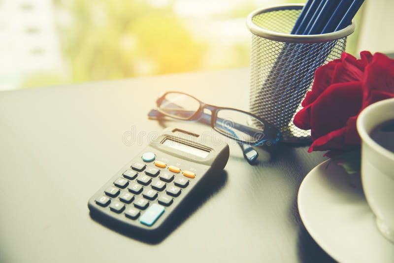Materiales de negocios con lápiz, calculadora, rosa roja, taza de café, papel de oficina imagen de archivo
