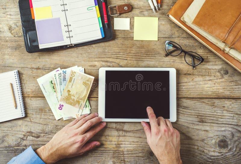 Materiales de oficina, artilugios y dinero en la tabla de madera imagen de archivo libre de regalías