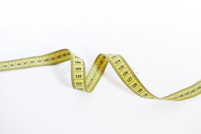 Materiales de oficina en el fondo blanco para medir la cintura foto de archivo