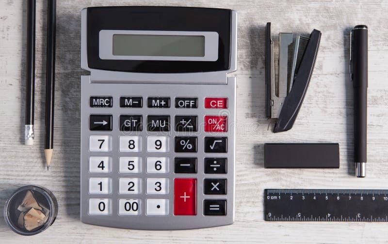 Materiales de oficina de la calculadora en fondo de madera fotografía de archivo