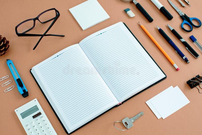Materiales de oficina organizados cuidadosamente alrededor del cuaderno fotos de archivo