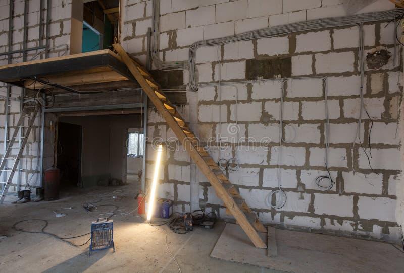 Materiali per le riparazioni, strumenti per il ritocco e lampada fluorescente in un appartamento che è in costruzione fotografia stock libera da diritti
