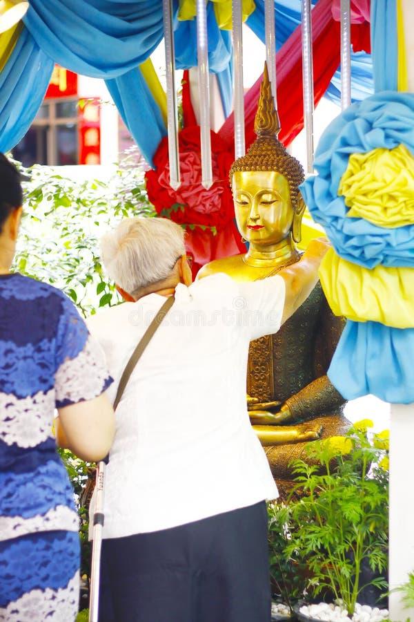 Materielfoto - duscha den buddha statyn i den Songkran festivalen arkivbild