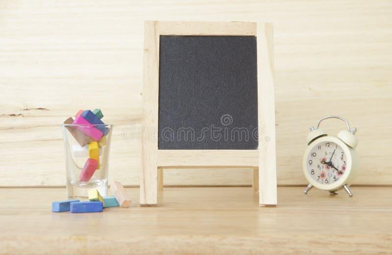 Materielfoto: Stilleben med den tomma svart tavla och kulöra chalks arkivfoton