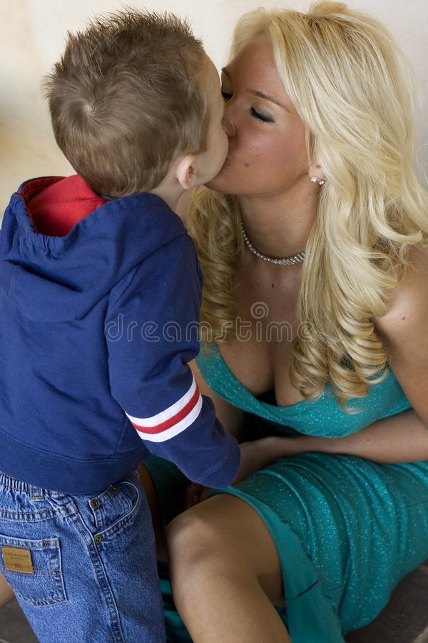 Maternal love. Image of my model kissing her son during a photoshoot. She had brought him along to the shoot with her stock images