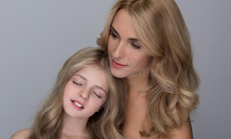 Cute little girl and attractive lady are feeling fondness. Maternal love. Portrait of lovely daughter is standing with closed eyes while putting head on stock photography