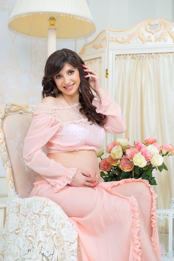 Maternidade bonita Grávido no vestido macio do pêssego senta-se na cadeira imagens de stock royalty free