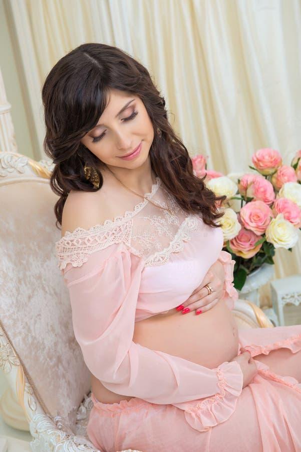 Maternidade bonita Grávido no vestido macio do pêssego senta-se na cadeira fotos de stock royalty free