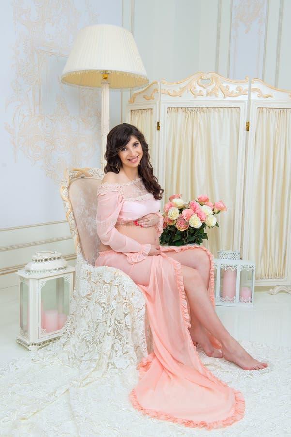 Maternidade bonita Grávido no vestido macio do pêssego senta-se na cadeira fotos de stock