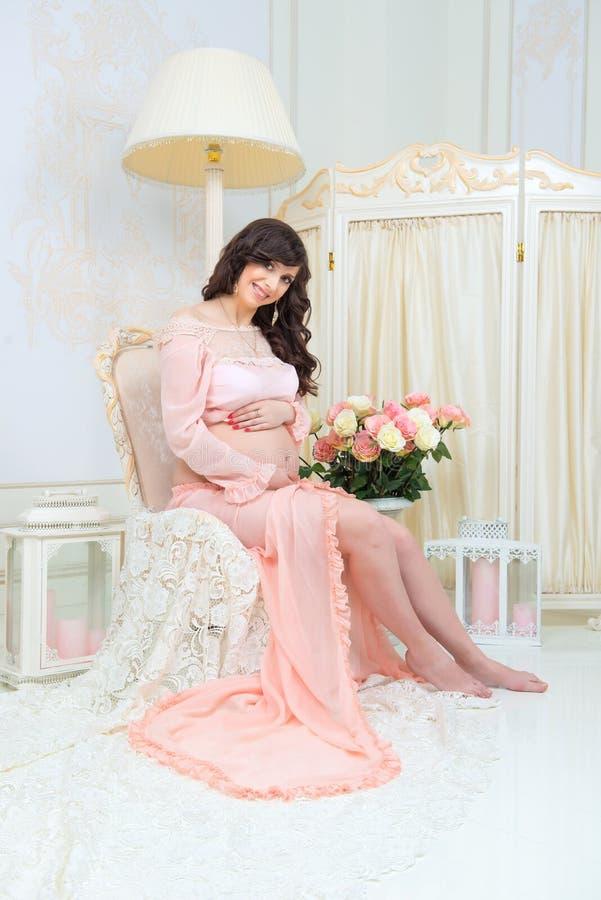 Maternidade bonita Grávido no vestido macio do pêssego senta-se na cadeira imagem de stock royalty free