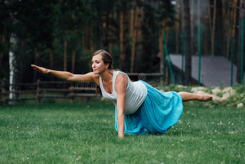 Maternidade pré-natal da ioga grávida que faz exercícios diferentes no parque na grama, respiração, esticando, estática fotografia de stock royalty free