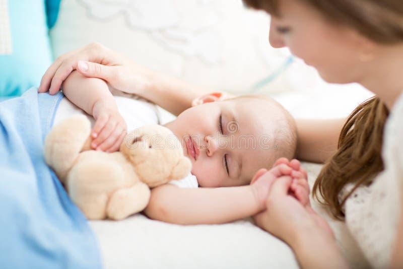 maternité parenthood Jeune mère regardant son bébé dormant dans le lit photo stock