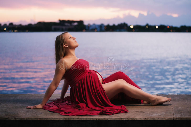 Maternity Portrait of a Woman Wearing Red. A seated, profile portrait of beautiful pregnant woman wearing a red maternity gown that slightly exposes her baby stock photography