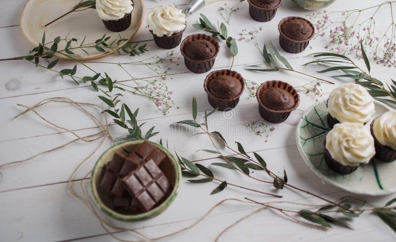 Matfoto, chokladmuffin och vit kräm för muffin i keramiska plattor av handwork på en vit träbakgrund med grönt eucal arkivfoton