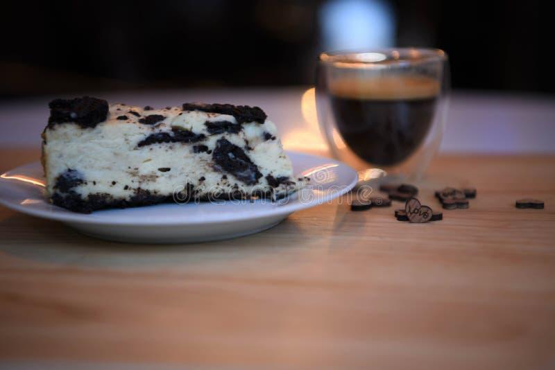 Matfotografi av ljusbrun ostkaka för hemlagad choklad med förälskelsehjärtagarneringar och suddighetsbakgrundskoppen kaffe royaltyfri bild