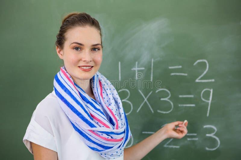 Mathématiques de enseignement de jeune professeur sur le tableau dans la salle de classe photos libres de droits