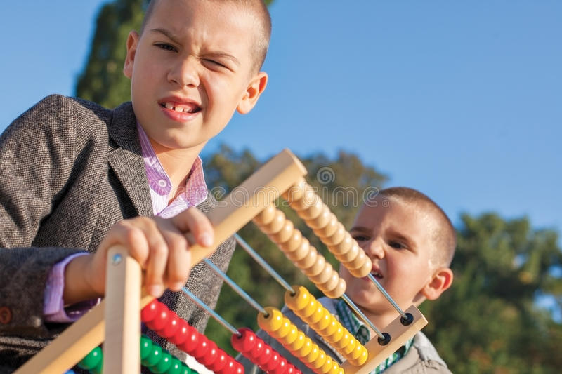 Math back to school abacus. Back to school two confused little boys playing with wooden abacus in the park. One arround seven, the ather four stock photography