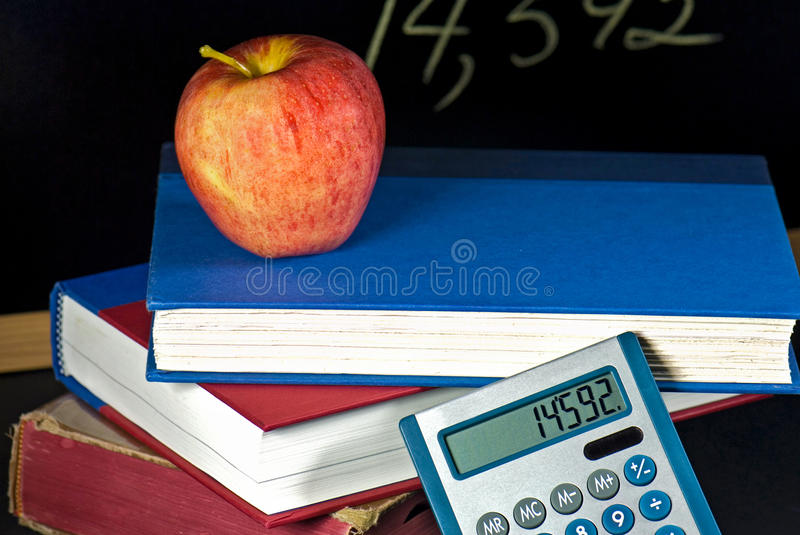 apple and calculator on school books royalty free stock photography