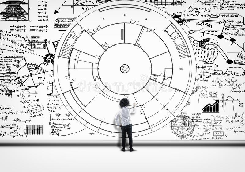 Math formulas solve. Student solving math formulas drawn on white wall stock image